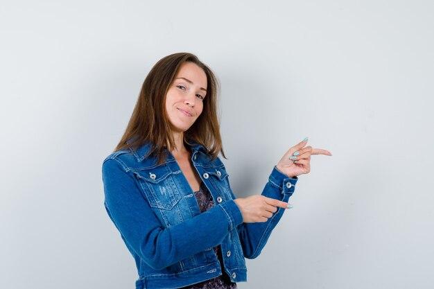 Jeune femme en chemisier, veste en jean pointant vers le côté droit et l'air heureux, vue de face.