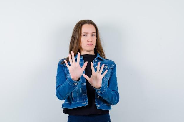 Jeune femme en chemisier, veste montrant un geste d'arrêt et l'air confiant, vue de face.