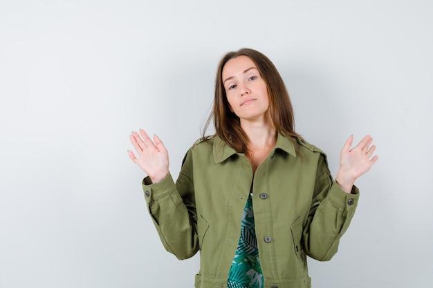 Jeune femme en chemisier, veste montrant les paumes en geste d'abandon et l'air confiant, vue de face.
