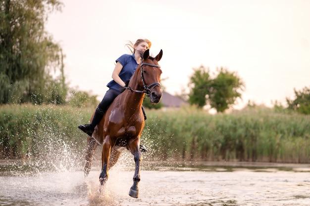 Une jeune femme à cheval sur un lac peu profond. un cheval court sur l'eau au coucher du soleil. soin et marche avec le cheval. force et beauté