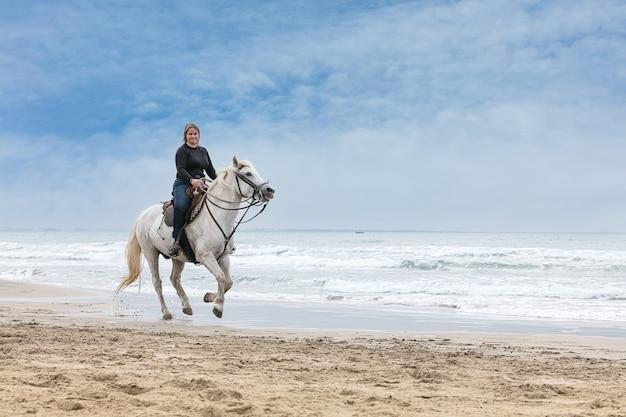 Jeune femme sur un cheval sur la plage un jour nuageux