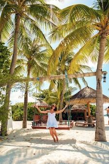 Jeune femme chevauchant une balançoire sur une journée d'été ensoleillée à l'ombre des palmiers