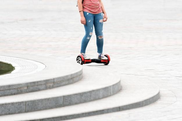 Jeune femme chevauchant un hoverboard sur la place de la ville. nouvelles technologies de mouvement et de transport. gros plan d'une planche à roulettes électrique à équilibrage automatique à deux roues. personnes sur scooter électrique à l'extérieur.