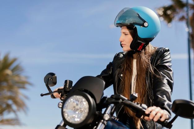 Jeune femme chevauche une moto