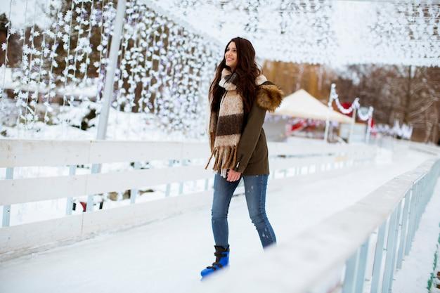 Jeune femme chevauche des patins à glace dans le parc