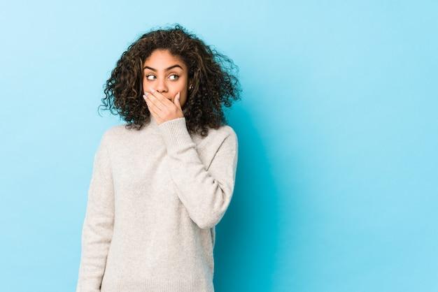 Jeune femme cheveux bouclés afro-américaine réfléchie à la recherche d'un espace vide couvrant la bouche avec la main.