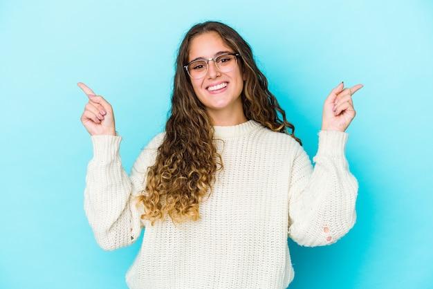 Jeune femme cheveux bouclés isolé pointant vers différents espaces de copie, en choisissant l'un d'entre eux, montrant avec le doigt