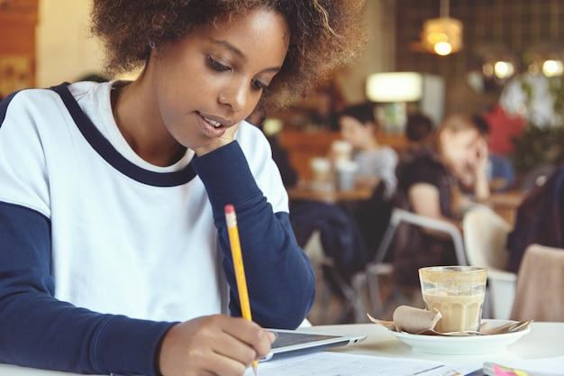 Jeune femme, à, cheveux bouclés, utilisation, tablette, dans, café