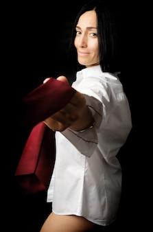 Jeune femme avec des cheveux noirs et une apparence caucasienne est vêtue d'une chemise blanche pour hommes et tire une cravate rouge