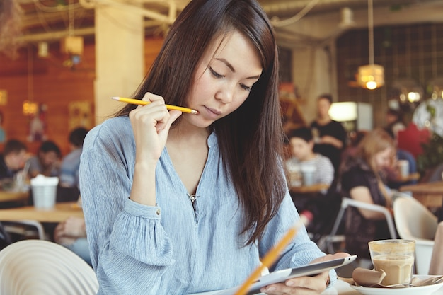 Jeune femme, à, cheveux noirs, utilisation, tablette, dans, café