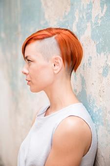 Jeune femme cheveux roux par le vieux mur