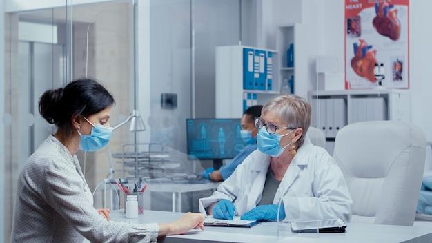 Jeune femme chez le médecin pendant la crise du covid-19, c'étaient des masques et des gants, parlant à travers un mur en plexiglas. consultation médicale dans le cadre du concept d'équipement de protection photo de la pandémie mondiale de sras-cov-2