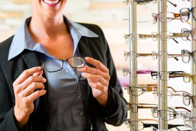Jeune femme chez un opticien avec des lunettes, elle pourrait être client ou vendeur