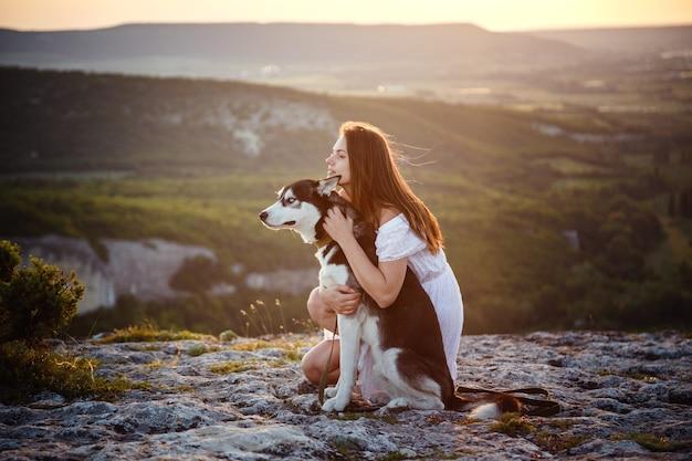 Jeune femme avec chien husky sur une journée ensoleillée assis en haute montagne