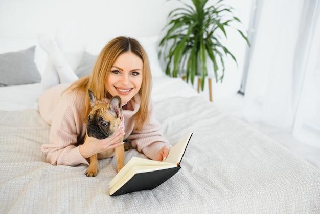 Jeune femme avec chien et livre de détente à l'intérieur à la maison, lecture.
