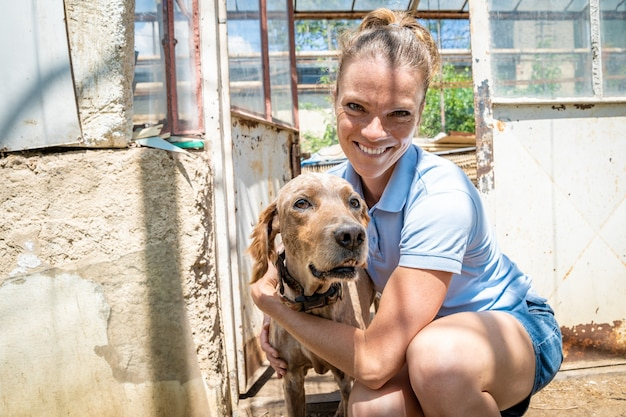 Jeune femme avec des chiens dans une serre à la ferme