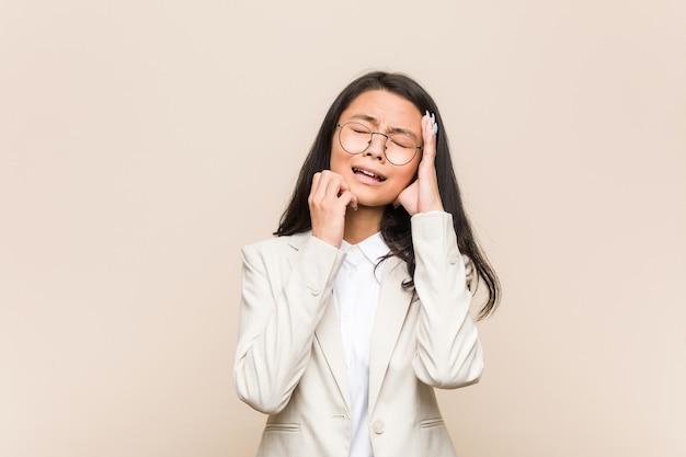 Jeune femme chinoise d'affaires pleurnichant et pleurant de façon inconsolable.