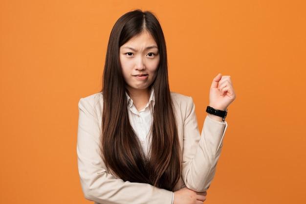 Jeune femme chinoise d'affaires touchant l'arrière de la tête, pensant et faisant un choix.