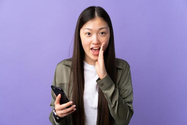 Jeune femme chinoise à l'aide de téléphone mobile sur violet isolé criant avec la bouche grande ouverte
