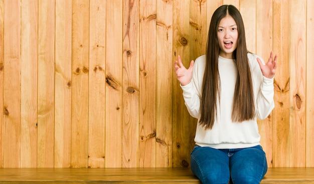 Jeune femme chinoise assise sur un endroit en bois hurlant de rage.