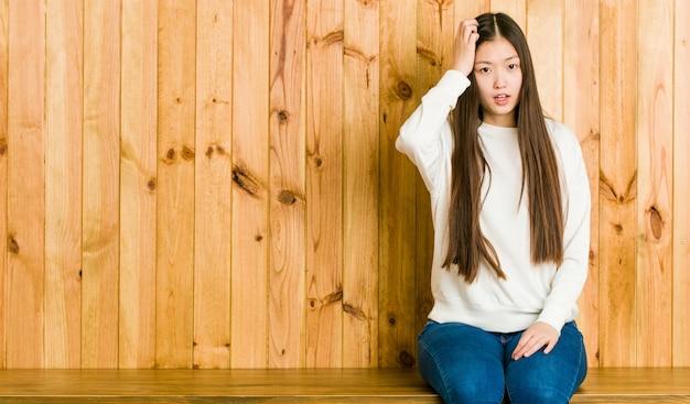 Jeune femme chinoise assise sur une place en bois étant choquée, elle s'est souvenue d'une réunion importante.