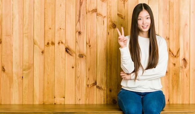 Jeune femme chinoise assise sur une place en bois montrant le numéro deux avec les doigts.