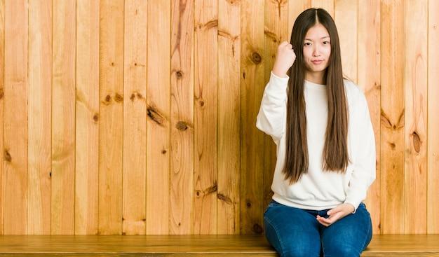 Jeune femme chinoise assise sur une place en bois montrant le poing