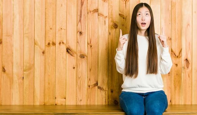 Jeune femme chinoise assise sur une place en bois pointant vers le haut avec la bouche ouverte.