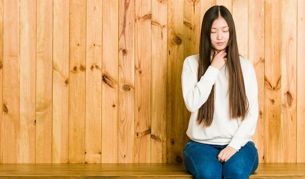 Jeune femme chinoise assise sur une place en bois souffre de douleurs dans la gorge en raison d'un virus ou d'une infection.
