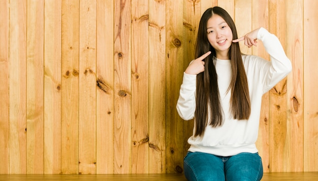 Jeune femme chinoise assise sur une place en bois sourit, pointe ses doigts vers la bouche.