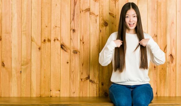 Jeune femme chinoise assise sur une place en bois surprise, pointant avec le doigt, souriant largement.