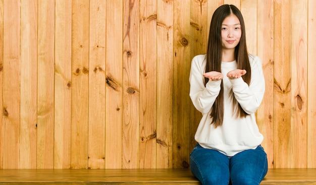 Jeune femme chinoise assise sur une place en bois tenant quelque chose avec des palmiers, offrant à la caméra.