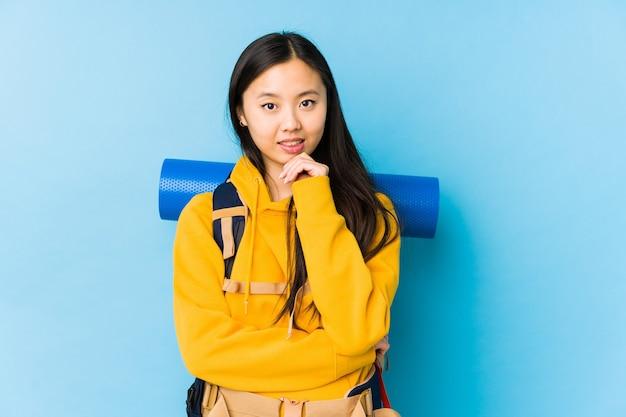 Jeune femme chinoise backpacker isolée souriante heureuse et confiante, touchant le menton avec la main.