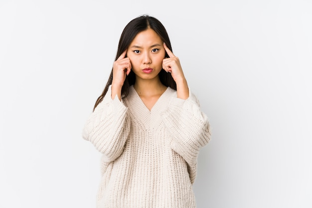 Jeune femme chinoise concentrée sur une tâche, gardant les index pointant la tête.