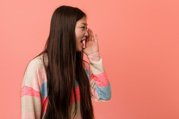 Jeune femme chinoise cool criant et tenant la paume près de la bouche ouverte.