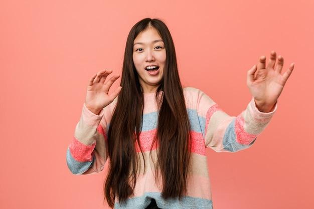 Jeune femme chinoise cool étant choquée en raison d'un danger imminent