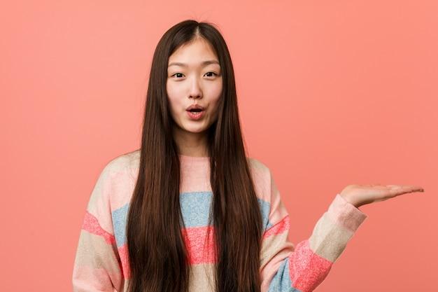 Jeune femme chinoise cool impressionné tenant sur la paume.