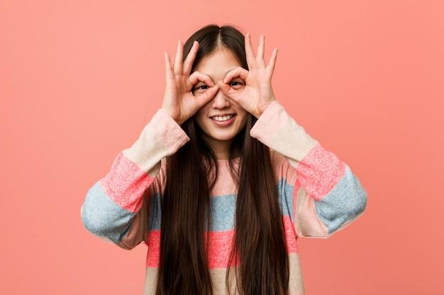 Jeune femme chinoise cool montrant un signe correct sur les yeux
