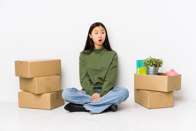 Une jeune femme chinoise déménageant dans une nouvelle maison étant choquée à cause de quelque chose qu'elle a vu.