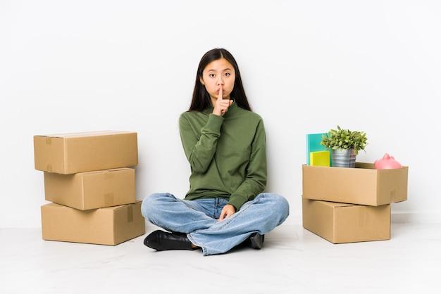 Jeune femme chinoise déménageant dans une nouvelle maison en gardant un secret ou en demandant le silence