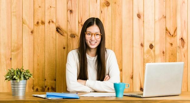 Jeune femme chinoise étudie sur son bureau en riant et en s'amusant.