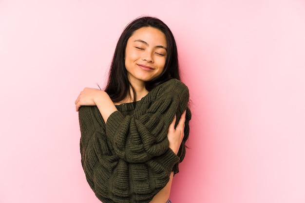 Jeune femme chinoise isolée sur des câlins roses, souriant insouciant et heureux.