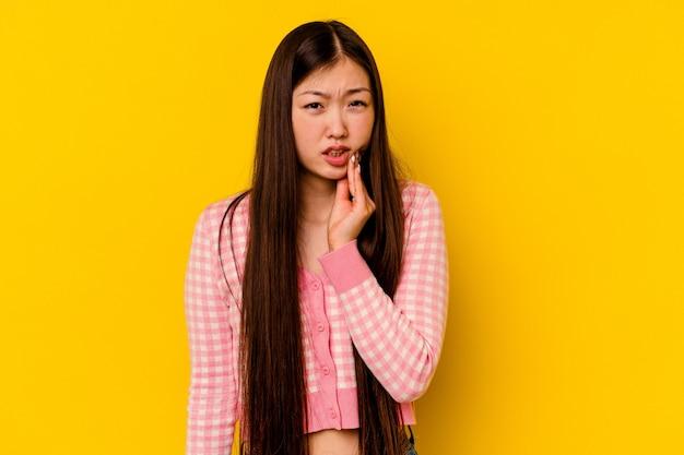 Jeune femme chinoise isolée sur fond jaune ayant une forte douleur dentaire, mal molaire.