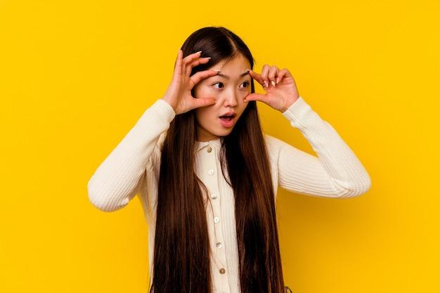 Jeune femme chinoise isolée sur fond jaune en gardant les yeux ouverts pour trouver une opportunité de succès.