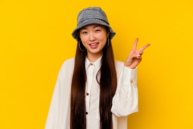 Jeune femme chinoise isolée sur fond jaune joyeux et insouciant montrant un symbole de paix avec les doigts.