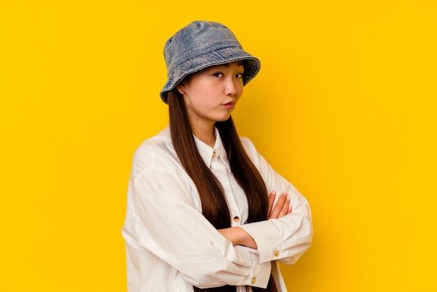 Jeune femme chinoise isolée sur fond jaune malheureuse à la recherche à huis clos avec une expression sarcastique.