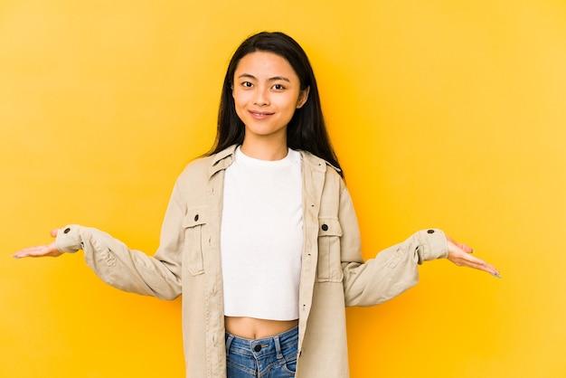 Jeune femme chinoise isolée sur fond jaune montrant une expression de bienvenue.