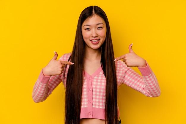 Jeune femme chinoise isolée sur fond jaune surpris en pointant avec le doigt, souriant largement.