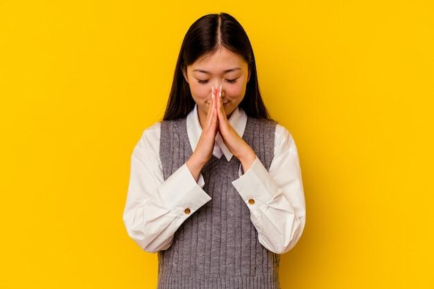 Jeune femme chinoise isolée sur fond jaune tenant la main en prière près de la bouche, se sent confiante.