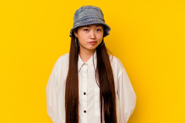Jeune femme chinoise isolée sur fond jaune, visage triste et sérieux, se sentant misérable et mécontent.